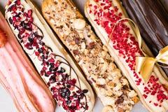 Söta och färgrika franska eclairs med berrys, choklad, muttrar, dekorerade med pilbågen Grupp av den franska efterrätten Eclairba Royaltyfri Fotografi