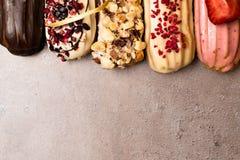 Söta och färgrika franska eclairs med berrys, choklad, muttrar och dekorerat med pilbågen Grupp av den franska efterrätten Eclair Royaltyfria Foton