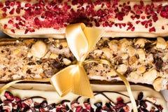 Söta och färgrika franska eclairs med berrys, choklad, muttrar och dekorerat med pilbågen Grupp av den franska efterrätten Eclair Royaltyfri Bild