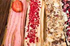 Söta och färgrika franska eclairs med berrys, choklad, muttrar Grupp av den franska efterrätten Eclairbakgrund Läcker färgrik ecl Royaltyfri Foto