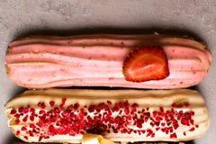 Söta och färgrika franska eclairs med berrys, choklad, muttrar Grupp av den franska efterrätten Eclairbakgrund Läcker färgrik ecl Royaltyfri Bild