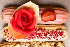 Söta och färgrika franska eclairs med berrys, choklad, muttrar Grupp av den franska efterrätten Eclairbakgrund Läcker färgrik ecl Royaltyfria Bilder