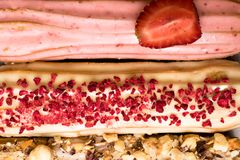Söta och färgrika franska eclairs med berrys, choklad, muttrar Grupp av den franska efterrätten Eclairbakgrund Läcker färgrik ecl Arkivfoto