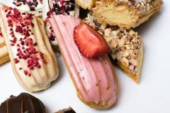 Söta och färgrika franska eclairs med berrys, choklad, muttrar Grupp av den franska efterrätten Eclairbakgrund Läcker färgrik ecl Royaltyfri Fotografi