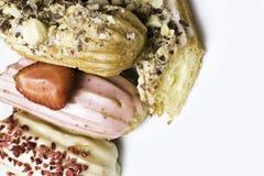 Söta och färgrika franska eclairs med berrys, choklad, muttrar Grupp av den franska efterrätten Eclairbakgrund Läcker färgrik ecl Arkivbild