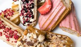 Söta och färgrika franska eclairs med berrys, choklad, muttrar Grupp av den franska efterrätten Eclairbakgrund Läcker färgrik ecl Arkivfoton