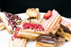 Söta och färgrika franska eclairs med berrys, choklad, muttrar Grupp av den franska efterrätten Eclairbakgrund Läcker färgrik ecl Fotografering för Bildbyråer