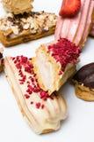 Söta och färgrika franska eclairs med berrys, choklad, muttrar Grupp av den franska efterrätten Eclairbakgrund Läcker färgrik ecl Royaltyfria Foton