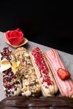 Söta och färgrika franska eclairs med berrys, choklad, muttrar Grupp av den franska efterrätten som dekoreras med marsipanrosen o Royaltyfria Foton