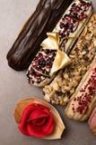 Söta och färgrika franska eclairs med berrys, choklad, muttrar Grupp av den franska efterrätten som dekoreras med marsipanrosen o Royaltyfri Foto