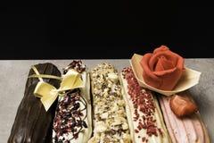 Söta och färgrika franska eclairs med berrys, choklad, muttrar Grupp av den franska efterrätten som dekoreras med marsipanrosen o Royaltyfria Bilder