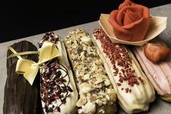Söta och färgrika franska eclairs med berrys, choklad, muttrar Grupp av den franska efterrätten som dekoreras med marsipanrosen o Royaltyfri Fotografi