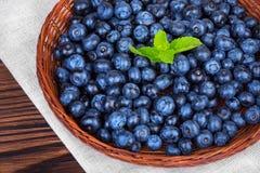 Söta och nya blåbär med mintkaramellen i en träspjällåda på en grå torkduk Naturliga blåa bär mycket av näringsrika vitaminer royaltyfria bilder