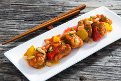 Söta och sura stekte grisköttstora bitar med grönsaker och jordnötter Fotografering för Bildbyråer