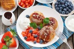 Söta ostpannkakor med bär och kräm för frukost Arkivbilder