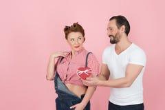 Söta par som väljer hjärtan Man i den vita t-skjortan som framlägger hans hjärta till brunettkvinnan i grov bomullstvill Grabben  arkivfoto