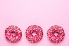 Söta rosa donuts med mångfärgade stänk på en rosa bakgrundslägenhet lägger royaltyfria bilder