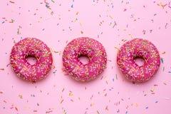 Söta rosa donuts med mångfärgade stänk på en rosa bakgrundslägenhet lägger arkivbilder