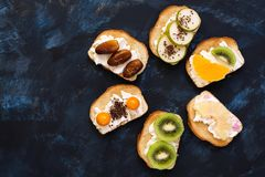 Söta smörgåsar i form av en blomma Rostade bröd med kräm- och olika frukter på en blå bakgrund Bästa sikt, utrymme för text arkivbild