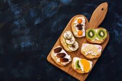 Söta smörgåsar med kiwin, tangerin, päron, ananas, data, physalis Efterrätt av sötsaksmörgåsar på en skärbräda bästa sikt, royaltyfri foto