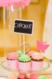 Söta smakliga kulöra muffin med suddig bakgrund på ett exponeringsglas Fotografering för Bildbyråer