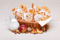 Söta tårtor i korgen, frukt och mjölkar garneringen fotografering för bildbyråer