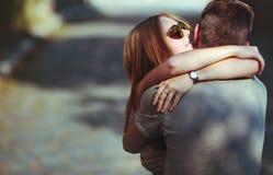 Söta tonåriga par som omfamnar på gatan. Fotografering för Bildbyråer
