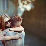 Söta tonåriga par som omfamnar på gatan. Arkivfoto