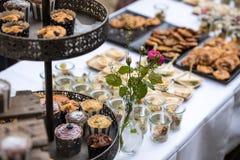 Söta trädgårdmottaganden - tabell med en vit bordduk, med olika sorter av sötsaker, kakor och mellanmål arkivfoto