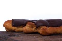 Söta tre chokladeclairs på vit Traditionella fransmankakor som lagades mat från chouxdeg, fyllde med en kräm Arkivbilder