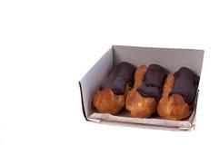Söta tre chokladeclairs som isoleras på vit Traditionella fransmankakor som lagades mat från chouxdeg, fyllde med en kräm Royaltyfri Bild