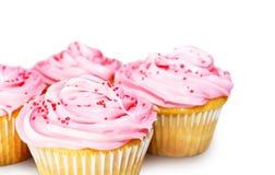 Muffiner med rosa glasyr på kaka Arkivbilder