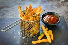 Sötpotatissmåfiskar i metallkorg med ketchup Arkivfoton