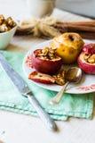 Sötsaken bakade äpplen med valnötter, kanel och honung, höst Arkivfoto