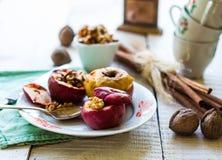 Sötsaken bakade äpplen med valnötter, kanel och honung, jul Royaltyfri Foto