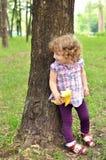 Sötsaken behandla som ett barn flickanederlag bak trädet Royaltyfri Bild