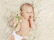 Sötsaken behandla som ett barn hemma att sova med nallebjörnen Arkivfoto