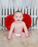 Sötsaken behandla som ett barn pojken som sitter med stor röd hjärta Arkivfoto