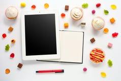 Sötsaker förlöjligar upp med anteckningsboken och minnestavlan Arkivfoton