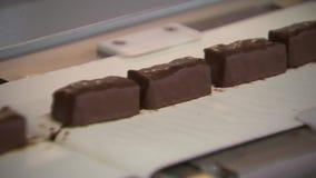 Sötsaker i choklad flyttar sig snabbt längs transportören arkivfilmer