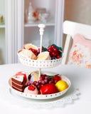 Sötsaker och fruktplatta på köket arkivfoto