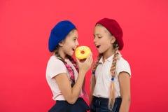 Sötsaker shoppar och bageribegreppet Enorma fans för ungar av bakade donuts Söt munk för aktie Flickor i baskerhattar rymmer den  arkivbild