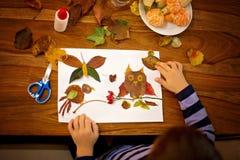 Sött barn, pojke som applicerar sidor genom att använda lim, medan göra konster royaltyfria bilder