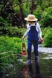 Sött barn, pojke som rymmer den röda gaslampan, lykta Arkivfoton