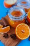 Sött driftstopp från apelsiner i små krus med ny cutted apelsiner, kanel och anice på den blåa tabellen Arkivbild