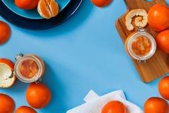 Sött driftstopp från apelsiner i små krus med nya apelsiner Arkivbild