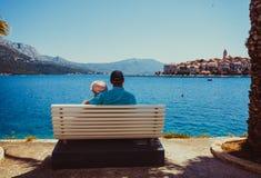 Sött gift par som sitter på en bänk nära havet royaltyfri foto