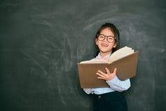 Sött lite engelsk lärare som använder studieboken arkivfoton