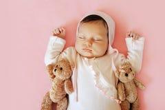 Sött lite nyfött behandla som ett barn att sova på filten med hans leksak för två björnar Arkivbilder