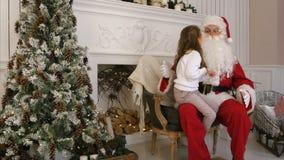 Sött liten flickasammanträde på jultomten sveper och beskriva honom vad hon önskar för jul arkivfoton